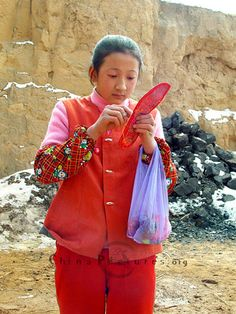 Village girl in the northern China doing embroidery during class interval