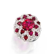 PLATINUM, RUBY AND DIAMOND RING, VAN CLEEF & ARPELS.  Of floral design, centered by an oval-shaped ruby weighing 4.09 carats, accented by 12 marquise-shaped rubies weighing 2.50 carats and numerous round diamonds weighing 3.40 carats, size 6½, signed Van Cleef & Arpels, numbered N.Y. 1858 S.O. With signed box.