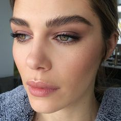 Soft mauve makeup look with bold lashes and full brows.