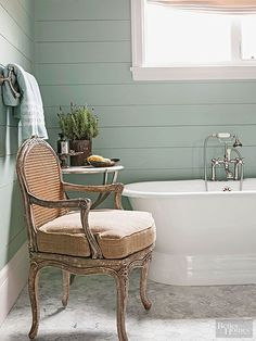 Both European and American country influences enhance cottage bathroom designs. This bathroom leans toward beachy thanks to the sea-green shiplap walls and marble floor, but it also accommodates French antiques. A flea market chair and elegant side table bring unexpected charm to the utilitarian space./ by stella