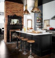 magnifique cheminée en briques, ilot cuisine noir, pan de mur noir, carrelage mur blanc, tabourets industriels, suspensions style loft industriel