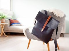 Custom made leather backpack with strap closure. Designed and handmade by Sas de Vries