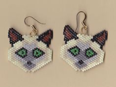 Beaded Siamese Cat Earrings. These cute beaded earrings are made using size 11 Delica glass seed beads in black, natural, greys, and blue. They come with surgical steel silver-tone ear hooks and measure about 2 inches in length.