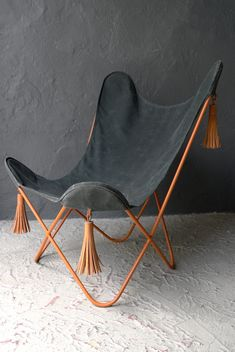 casamidy mariposa chair in waxed canvas and wrought iron saddle leather tassels.