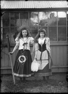 Outdoors portrait of two unidentified young women in fancy dress costumes, one as a sailor with a small 'City of Crafton, Sydney' lifebuoy and oar, and the other as a [gypsy or milkmaid?], probably Christchurch region