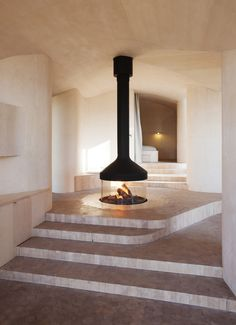 """The layout revolves around a central """"campfire"""" that burns beneath a suspended mantel. Since it's located at the access level, the fireplace's flickering warmth can be enjoyed throughout the house. The surrounding floor is covered with hexagon tiles cut from marble, which transition into tiles made of birch log in the rest of the house."""