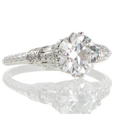 An Art Deco platinum solitaire ring featuring a 1.18ct modified brilliant cut diamond accompanied by a GIA certificate held in four split claws that taper down the pierced and diamond set gallery with millegrain highlights that follow down the incorporated shoulders bordering a fine row of graduated diamonds tapering to meet the detailed band engraved with a double row of overlapping leaves meeting the plain polished back. #RutherfordJewellery #Melbourne