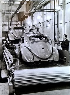 Bild 10 - Here the bodies are being dipped into a tank of primer before going on to receive the finishing coats that will give the cars their final, shining color and make them impervious to all weather conditions.