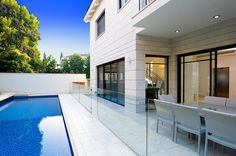 perfect example of a modern style lap pool in a small area made to look larger with the used of glass fencing.
