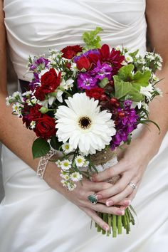 Wedding bridal bouquet with red roses, a white daisy, and purple accents.