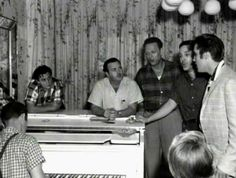 Elvis jamming in the music room at Graceland in August 1957. If you look very carefully you will see a mirror above the piano on the left. The Presley's bought this when they were living in Audubon Drive, there is a photo of Gladys using it, one of Elvis using it and just recently one of Lisa Marie using it. The mirror is still hanging there to this day.