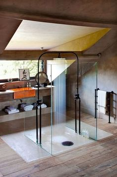 Love the openness of this - cool shower!!!! An industrial style bathroom with a centered glass-enclosed shower with a centered shower head. A towel rack is formed with pipes.