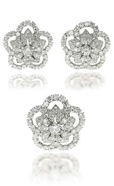 A SET OF DIAMOND FLOWER BROOCHES, BY CARTIER.  Composed of three openwork diamond-set flower clips, can be adapted on a gold ropework bracelet, the larger flower can be used as a clasp on a three-row cultured pearl necklace, brooches 3.6 cm and 3.3 cm, bangle inner circumference 16.5 cm, necklace 52.2 cm, with French assay marks for gold, in two red velvet Cartier pouches  Brooches and bracelet signed and with maker's marks for Cartier Paris, no. 010010 (brooches)