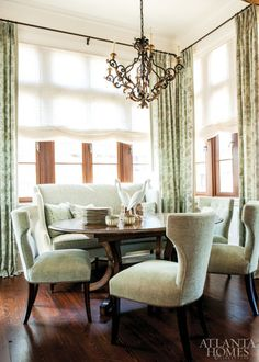 """""""The dining room is a very small space so you really notice every detail,"""" says Weaks. """"We had to capitalize on every square inch of it."""" The banquette was custom made for the alcove by Edward Ferrell + Lewis Mittman and upholstered in a Henry Calvin fabric, both from Ainsworth-Noah & Associates. The dining table is by New Classics Creations, and the chairs are by Edward Ferrell + Lewis Mittman. Iron-and-gilt chandelier, Robuck & Company."""