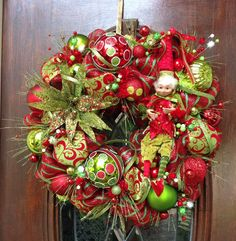This 24 inch red and lime green stripe deco mesh wreath has a cute Christmas Elf on the right side with a whimsical Poinsetta on the left side.