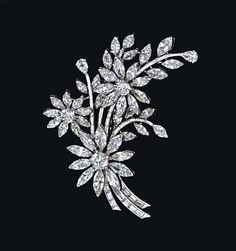 A DIAMOND FLOWER BROOCH   Designed as three circular and marquise-cut diamond flowerheads, set en tremblant, extending marquise-cut diamond leaves, to the baguette-cut diamond stem, mounted in platinum