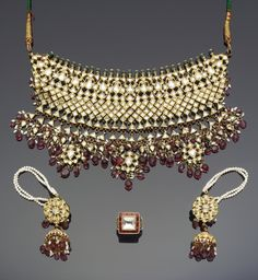 An Indian diamond and tourmaline-set enamelled gold Fringe Necklace and Earrings   composed of a band of interlocking floral elements with an emerald-mounted finial above, below a band of square elements joined to form a diamond-shaped pattern, below a fringe of openwork floral pendants with tourmaline and seed-pearl fringe, verso enamelled in polychrome with floral designs; the earrings with an openwork floral pendant with a hemispherical section suspended below, decorated ensuite