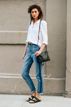 French styles pride themselves in looks that look timeless. Simple pieces like a white button down and blue jeans are such, but accessorized by her belt, bag, and choice of slippers.