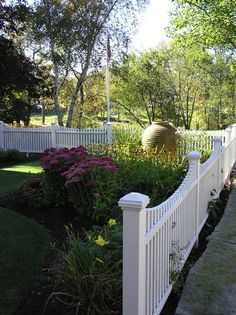 White picket fence design with landscaped lawn, various colorful flowers, and flagpole. Beautiful!