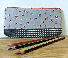 """This pencil case is made using 100% cotton fabric and lined with interfacing to add durability.Fabric used includes Walk in the Woods by Aneela Hoey, lined with red cotton fabric. The zipper is orange. Ideal for holding pencils, pens, school supplies or small make up accessories. Dimensions 22cms x 12 cms ( approx 9"""" x 5"""")Made in a smoke free home.Product care: Avoid putting in a washing machine, spot cleaning is preferable, dry flat and iron on a medium heat. Shipping to Ireland €1.20…"""