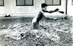 Photo documenting Kazuo Shiraga performing Challenging Mud at the 1st Gutai Open Air Exhibition, Tokyo.