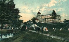 A view looking west across the grounds of Luna Park in 1910. The roller coaster and several other buildings occupy the top of a small hill. The corner of a lake can be seen in the lower left foreground. A considerable crowd has gathered around the lake and on the steps leading up to the roller coaster.