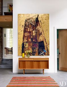 In the living room, an Enoc Perez painting surmounts a 1950s Hille credenza topped by an Eddie Martinez| archdigest.com