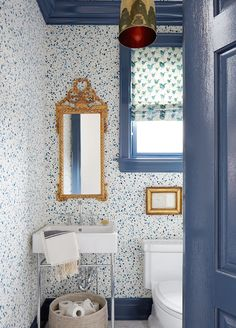 A blue door opens to a blue bathroom features a glossy blue painted ceiling over walls clad in Hinson & Company Paint Splatter Wallpaper lined with an ornate gold mirror over a round woven basket filled with toilet paper tucked under a 2-leg washstand with white porcelain sink draped in a Turkish hand towel next to a blue framed window dressed in blue birds fabric situated over a toilet illuminated by an antique brass dome light pendant, Arteriors Savoy Pendant.