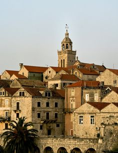 Korcula Island, Croatia has white stone walls, red spanish tile roofing, ornate carvings, arched openings, and a central bell tower.