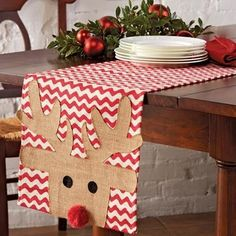 Printed burlap table runner features reindeer applique with red yarn pom-pom…