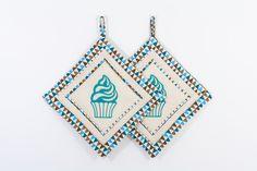 Die Topflappen-Cupcake sind mit einem Cupcake-Motiv bestickt und mit den Farben blau, braun und beige im Patchwork-Stil gestaltet.