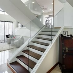 Possible solution to staircaise - addresses safety, design and functional issues.Swap stainer steel for glass railings and safer, plus fill in gaps with MDF and encase under stairs.