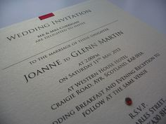Ivory and Red triple mounted wedding invitations with red ribbon between the card layers