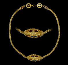 ROMAN GOLD NECKLACE AND PENDANT Circa 3rd-4th century AD. A gold necklace comprising a gold trichinopoly band with tubular terminals set with filigree collars and four tear-shaped cabochon garnets, with attachment loops in the form of a round-section bar with recurved and hoop ends set with an openwork filigree annulate with granule detailing; the pendant a free-running hollow biconical tube with applied filigree heart designs and cabochon tear-shaped garnets .