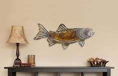 """Rustic, edgy and contemporary. The Fish Metal Art is hand-cut from 18 gauge steel, then colored with heated torch and clear coated for both indoor and outdoor display. Details Dimensions: 23"""" X 9"""" Mat"""