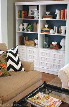 Bookcase Back Panel Ideas: Painting the back panel of an all-white bookcase in a contrasting color gives it depth and helps the accessories take center stage.