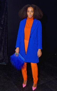 Solange posed backstage at the Milly by Michelle Smith Fall/Winter 2014 fashion show on February 10 in New York wearing a blue coat by the designer, an orange turtleneck and trousers, and pink heels.