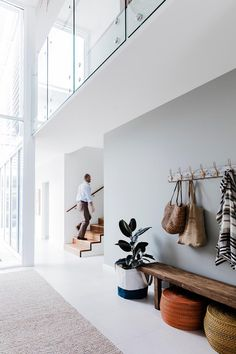 Retirees Build Beachside Retreat In Newcastle Rob makes his way up the spotted-gum steps. Above him, a glass balustrade allows extra light into the upstairs hallway. Upstairs Hallway, Entry Hallway, Hallway Ideas, Modern Hallway, Hallway Designs, Modern Staircase, Coastal Living Rooms, Home And Living, 2018 Interior Design Trends