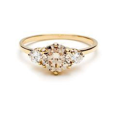 "Brides.com: . 3 stone ""Hazeline"" 14K yellow gold with 1.2 carat champagne diamond center and white diamond side stones, $10,500, Anna Sheffield  See more round-cut engagement rings."