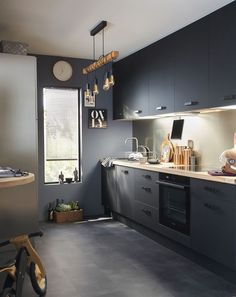 Ce sol effet béton est en parfaite harmonie avec le mobilier de cette cuisine noire