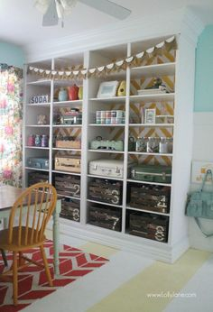 Built in shelving storage that uses painted crates and old luggage to showcase and office supplies organization