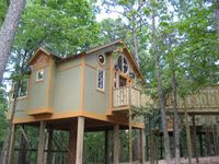 Eureka Springs, AR - At the Grand Treehouse Resort, all of the treehouses have 32-inch flat screen televisions, wet bars, stereo systems, DVD players, Jacuzzi tubs for two and fireplaces. Other amenities include walk-in showers, irons, ironing boards, hair dryers, stained glass windows, luxury linens, WiFi, and homemade desserts available upon arrival.