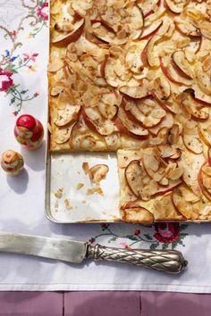 Saftige Äpfel liegen auf einem Bett aus Quarkteig und Pudding, abgerundet wird der Apfel-Quark-Kuchen mit Kardamom und Mandeln.