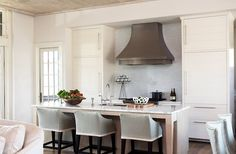 kitchen: upholstered barstools + vent hood similar slow curve in their shapes. Nice subtle detail.