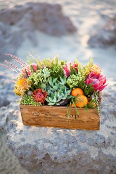 Use old crates and fill them with fruit and flowers - we could stencil table numbers or a fun table name on them!