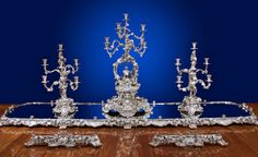 THE QUEEN ADELAIDE GARNITURE DE TABLE. A MAGNIFICENT VICTORIAN SILVER TABLE GARNITURE BY ROBERT GARRARD London, with marks for R and S Garrard and R and S Garrard and Co., 1839-40 and 1852  Comprising a large silver mounted mirror plateau, in four sections with two extra end sections, the boarder cast and chased and applied with vines and scrolls on massive scroll supports, embellished with the arms and supporters and cypher of Queen Adelaide