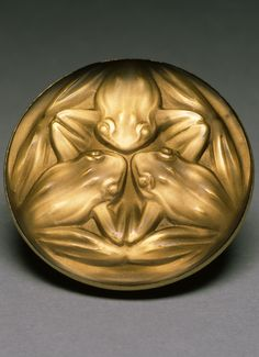 An early Art Deco amber coloured glass and gilded brass 'Frogs' brooch, by René Lalique, circa 1911. #Lalique #ArtDeco #brooch
