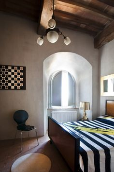 I love few, bold decorations - striped bedroom cover, Kartell lamps, colour choice for kitchen and canvas #umbria #luxury