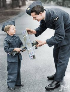 A boy offers his toy plane to the RAF after a national request for scrap metal for the making of warplanes (ca. 1940)