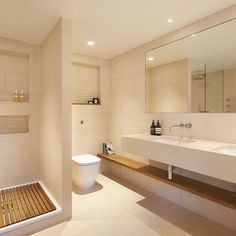Beautiful en suite bathroom at a private house. Featuring natural stone wall and floor tiles. Shower suite and his and hers sink were crafted from the Solar range.